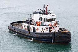 A tug boat stands ready to help ships in the Panama Canal