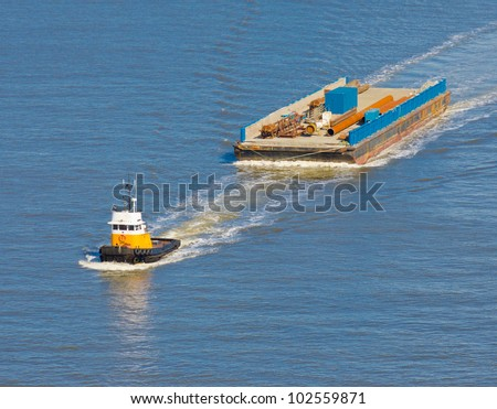 A tug boat towing barge.