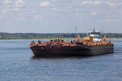 A tug carrying a liquid barge on the Volga River