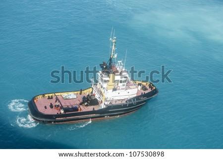 A tugboat cruising in deep blue water of Bermuda bay