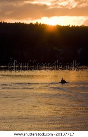 A tugboat heading east into the rising sun