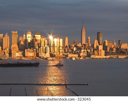 A tugboat pulls a barge along the Hudson River as the sunset reflects off the New York City skyline.