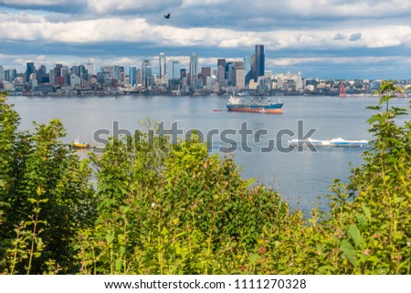 A tugboat pulls a barges in front of the Seattle skyline.