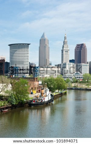 A tugboat sits moored along the bank of the Cuyahoga River with the downtown area of Cleveland, Ohio in the distance