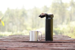 a tumbler mug and a cup in the wooden table