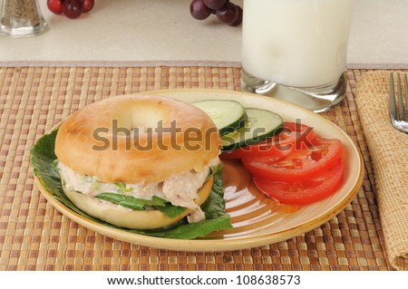A tunafish sandwich on a bagel with sliced tomato and cucumber