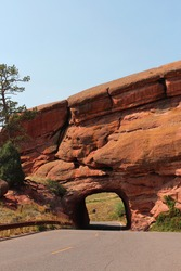 A tunnel carved through red sandstone for a two lane road in Red Rocks State Park in Colorado, USA