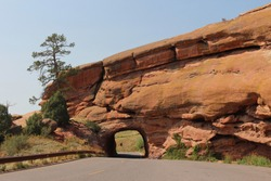 A tunnel carved through red sandstone for a two lane road with an adjacent parking lot in Red Rocks State Park in Colorado, USA