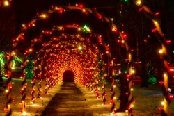 A tunnel of festively lighted Christmas arches decorates a walkway on a small town public square