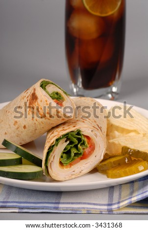 A turkey and swiss cheese wrap with soft drink