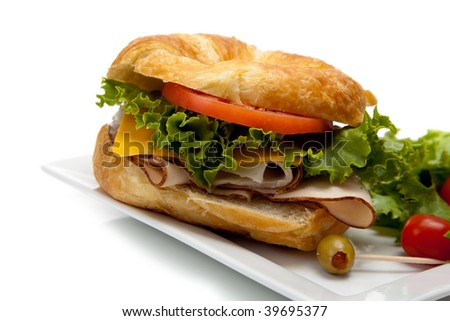A turkey sandwich on a croissant with lettuce, cheese and tomatoes sitting on a plate with salad and olives on a white background