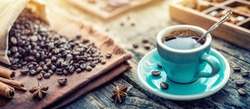 A turquoise cup of aromatic black coffee and coffee beans on the table. Morning Coffee Espresso for breakfast in a beautiful turquoise cup.