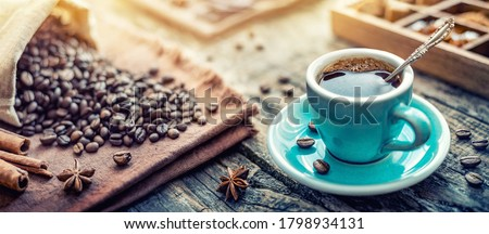 A turquoise cup of aromatic black coffee and coffee beans on the table. Morning Coffee Espresso for breakfast in a beautiful turquoise cup. Stockfoto ©