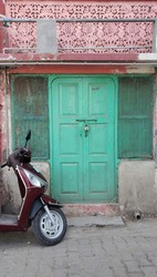 A turquoise doorway and a scooter in the streets of Rishikesh, India