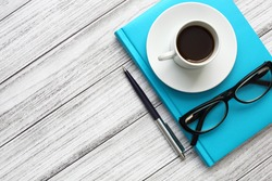 A turquoise notebook, a white coffee cup, glasses, and a ballpoint pen on a wooden background. Close up, top view, diagonal composition. Office picture.