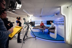 A TV show being filmed in a studio. The presenters are sitting on the studio sofa and talking to each other while the camera crew films them with film cameras.