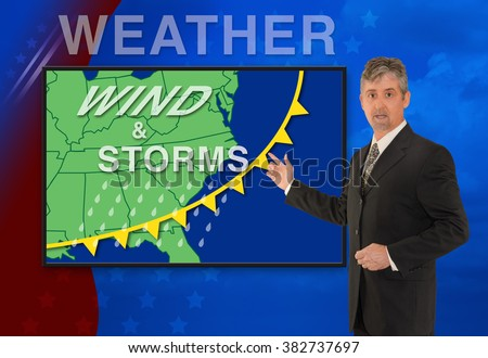 A tv television news weather meteorologist anchorman is reporting with a Wind & Storm graphic over a stormy black cloud photo on the monitor screen.