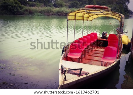 A twelve seater FRP Motor Boat for recreational and adventurous activities for tourists anchored on the bank of the Godavari river near Nashik in India.