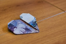A twenty pound note, folded in to an origami heart, and placed on a wooden surface.