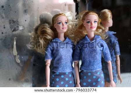 A twin dolls beside the mirror