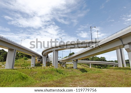 A twisty complicated elevated highway system through a grassy field against a blue cloudy sky.