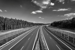 A two-lane asphalt expressway crossing the forest in Poland, black and white