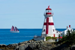 A two-masted schooner sails past the Head Harbour Lightstation on a clear, calm day. Also known as the East Quoddy Head. Campobello Island, New Brunswick, Canada.