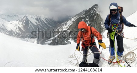 A two mountain climbers, a girl and a man, with rope on the slope. Ascent on Metallurg Peak. Altai Republic, Russia #1244108614