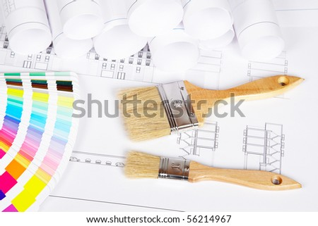A two paintbrushes and color guide over the house plan. Shallow depth of field