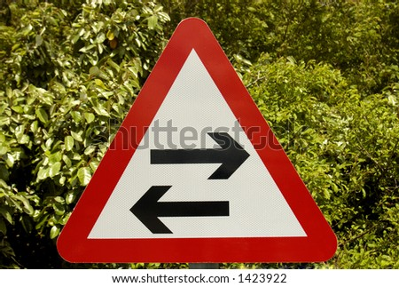 A two-way sign, arrows pointing in opposite directions, on a green leafy background. Clipping path included so sign can be isolated.