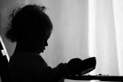 A two year old girl is sadly looking into her empty bowl wishing she had more to eat. / Hunger