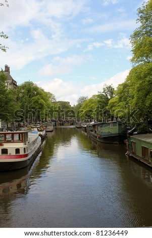A typical Amsterdam canal with boat houses and a brige