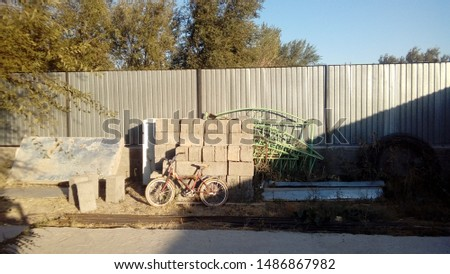 A typical aul yard from the inside. At the fence of corrugated board, a bicycle and miscellaneous utensils #1486867982