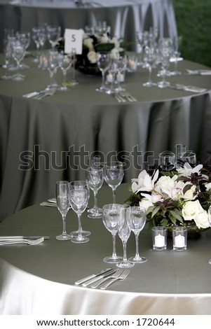 a typical dinner table setting, with a shallow depth of field with the focus on the foreground table, with the other tables fading out of focus