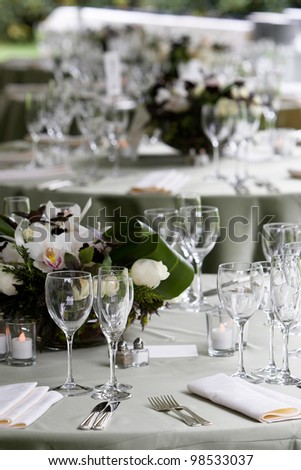 A typical dinner table setting with a very shallow depth of field with the focus on the silverware and glasses and the other tables fading out of focus