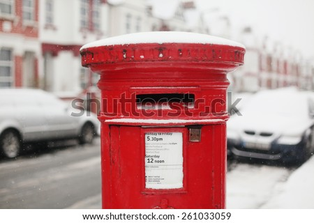 A typical English red letter (post) box covered in snow on the street of London.\ 10th of January, 2013