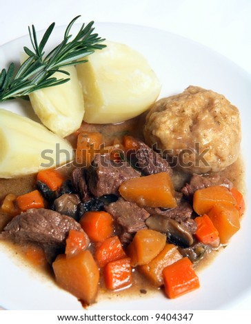 A typical English-style beef stew, containing carrots, swede (rutabega) and mushrooms, served with suet dumpling and boiled potatoes, with a sprig of fresh rosemary.
