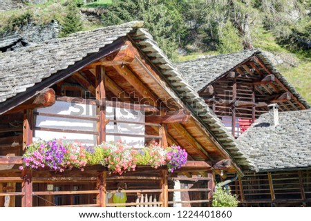 A typical German speaking Walser lodge, made of stone with board protected wooden balconies, in summer, in Val d'Otro valley, Alps mountains, Italy Foto stock ©