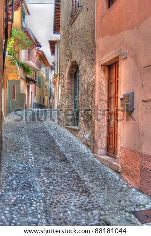 A typical Italian back street with cobbled roads and colorful buildings found in Tuscany, italy.