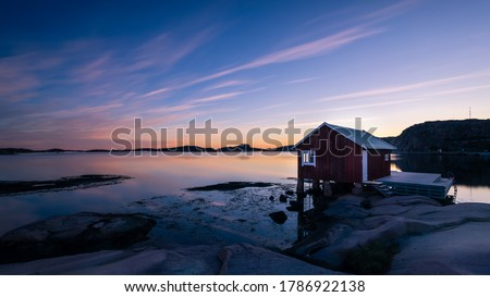 A typical red boat house with a colorful sky with reflections in the ocean on the Swedish west coast, Bohuslän Foto stock ©