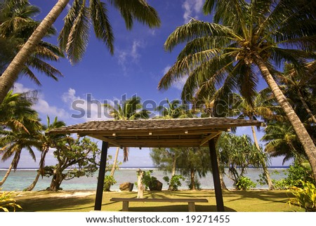 A typical roadside shot in the tropical Polynesian island of Rarotonga (Cook Islands) featuring lagoon, beach, palm trees and road shelter.
