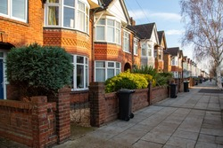 A typical row of English terraced houses with wheelie bins outside on the pavement