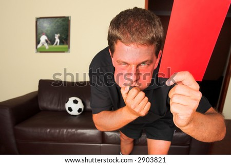 A typical sports fan as a referee in his sitting room, blowing a whistle and showing a red card or penalty card to send off an offending player. Cricketers on image in background by same artist.