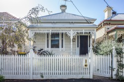 A typical Victorian era independent residential house in Australia. Facade of an Australian home with verandas sporting cast iron lacework. Roofs made from corrugated iron. Melbourne, VIC Australia.