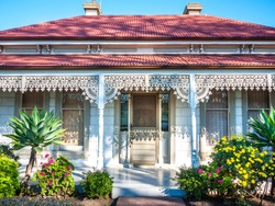 A typical Victorian era residential house in Australia. Facade of an Australian home with verandas sporting cast iron lacework. Roofs made from corrugated iron. Melbourne, VIC Australia.