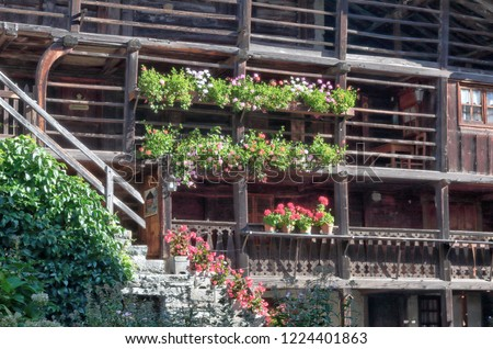 A typical Walser lodge, made of stone and  with board wooden balconies with flower planters and staircase, in Val d'Otro valley, Alps mountains, Italy Foto stock ©