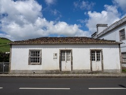 A typical white house beside the road in the town of Santa Cruz das Flores. With a blue sky with clouds. Flores Island.