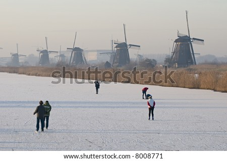 A typical winter scene in The Netherlands: people having fun on the ice between the world famous windmills of Kinderdijk.
