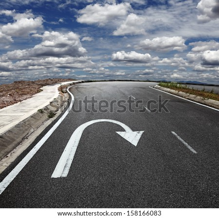 A U turn arrow traffic symbol imprint on a lonely asphalt road against a blue cloudy sky.