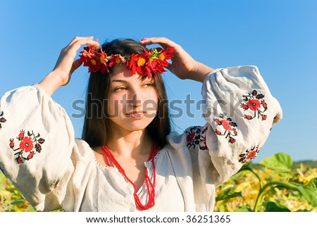 A Ukrainian woman in an authentic 19th century garment adjusting her garland made of live flowers in a sunflower field